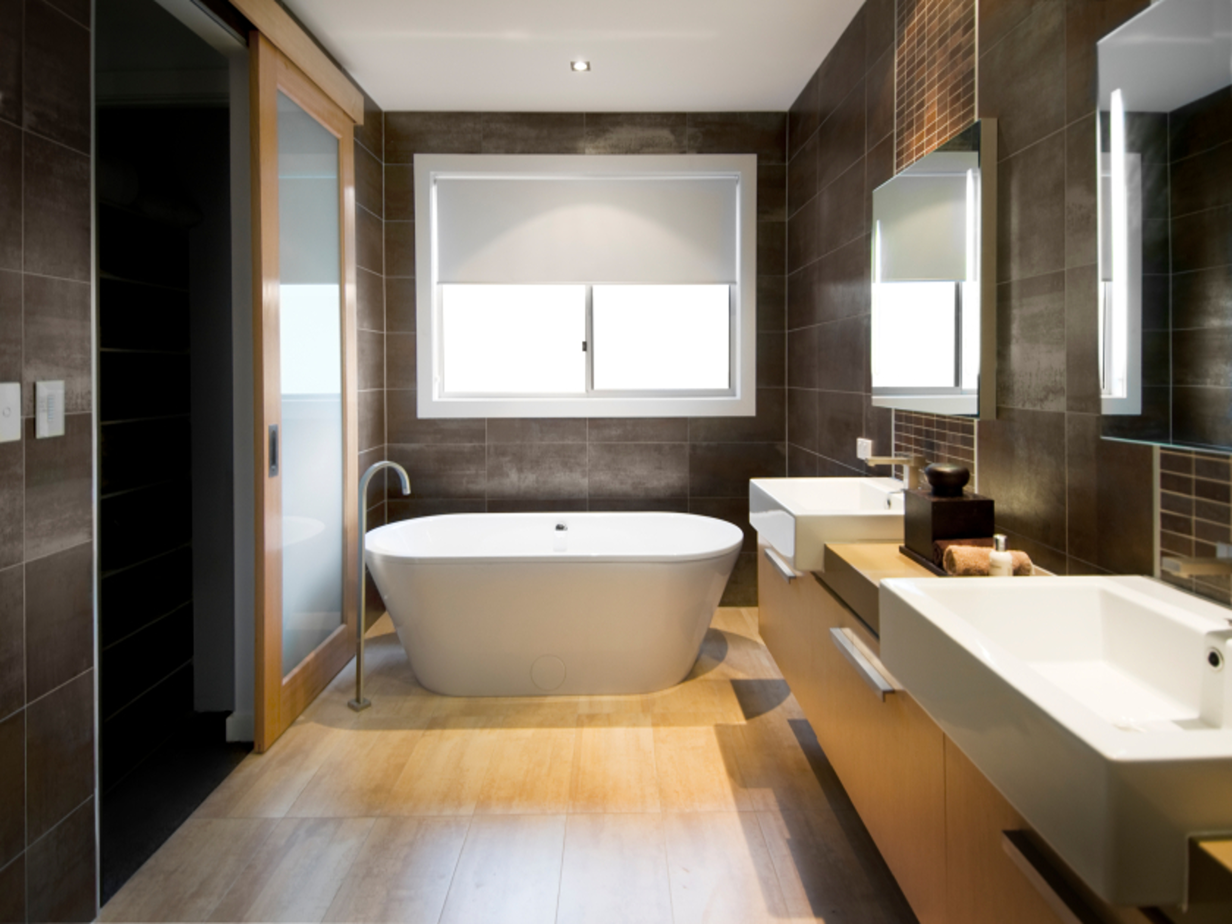 Australian Luxury bathroom with brown tiles and hardwood floor, focusing on a free standing bath. Clipping path around the windows and reflections in mirror/door.